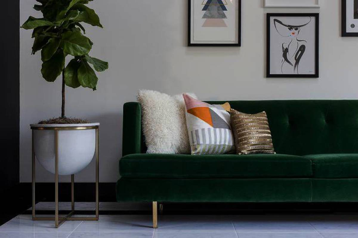 An emerald green sofa against a soft gray backdrop becomes focal point in the room.