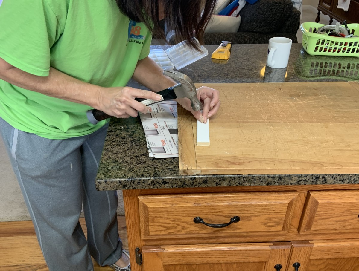 Putting a starter nail in the top rail board to make it easier to install. It was easier to start the nail on the counter rather than on the horizontal top rail.