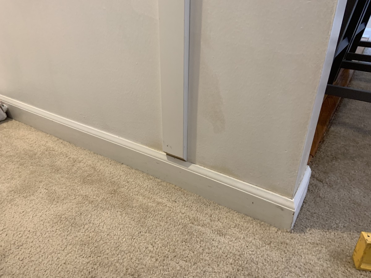 """Installation of a vertical slat (1"""" x 3""""). Note how the bottom of the slat is cut at a 45° angle to give nice transition to the bottom baseboard that already existed."""