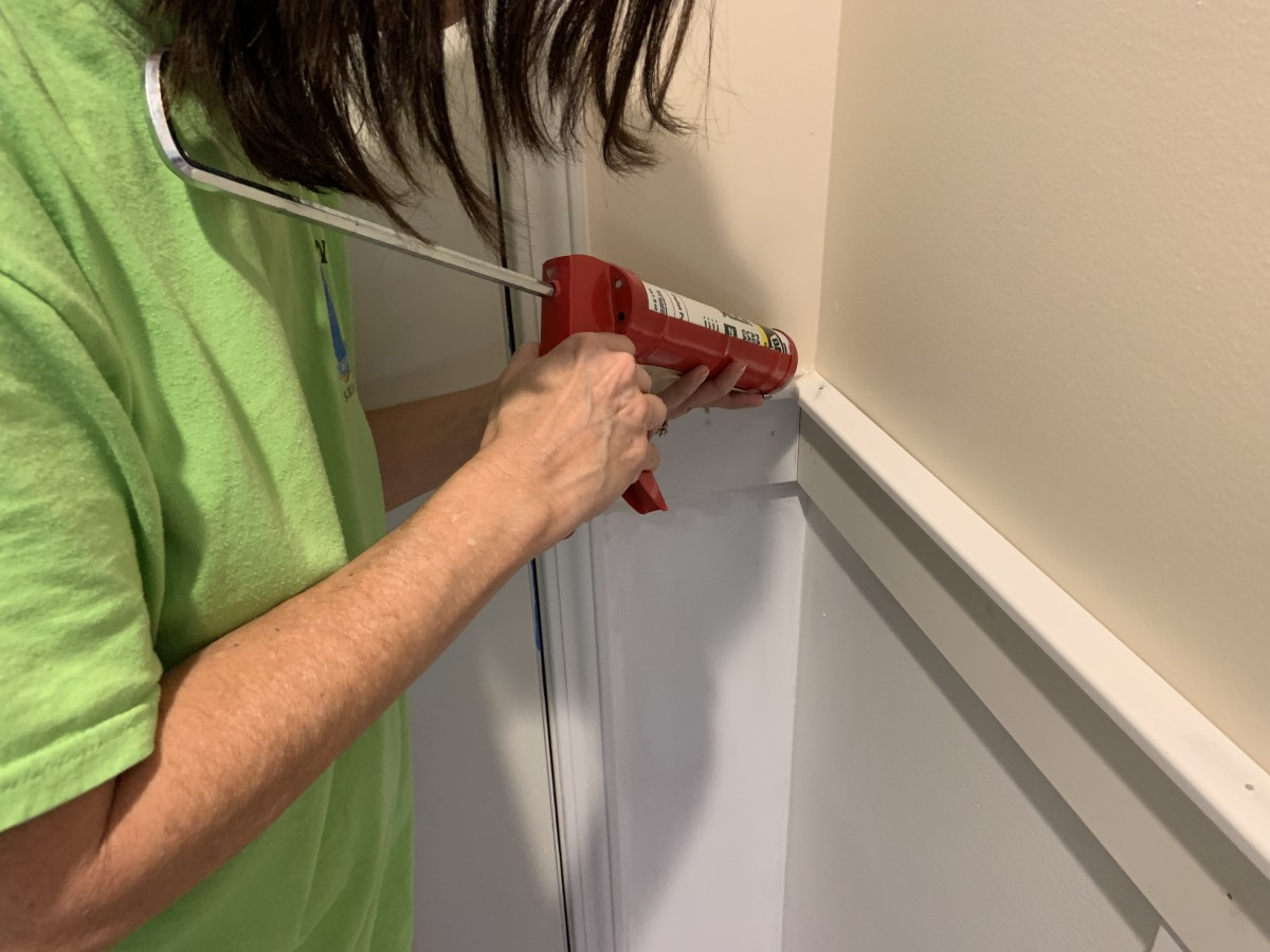 Applying caulk to the cracks in the corner to get it ready to paint. We had to put a small amount of caulk over the countersunk nails.