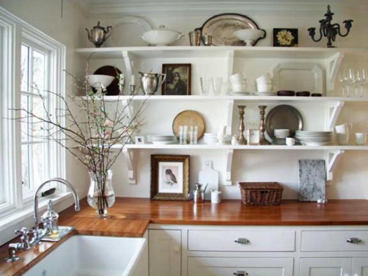A farmhouse kitchen has open shelving, butcher block counters and a big, deep apron front sink.