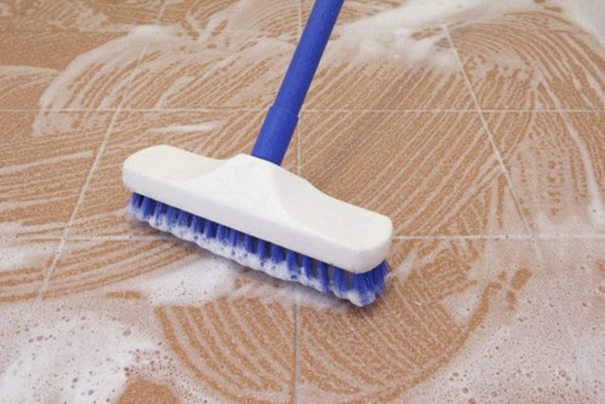 Scrub stone, ceramic or porcelain tiles with a stiff brush and heavy-duty cleaner. Consider purchasing a steam cleaner or hire a professional.
