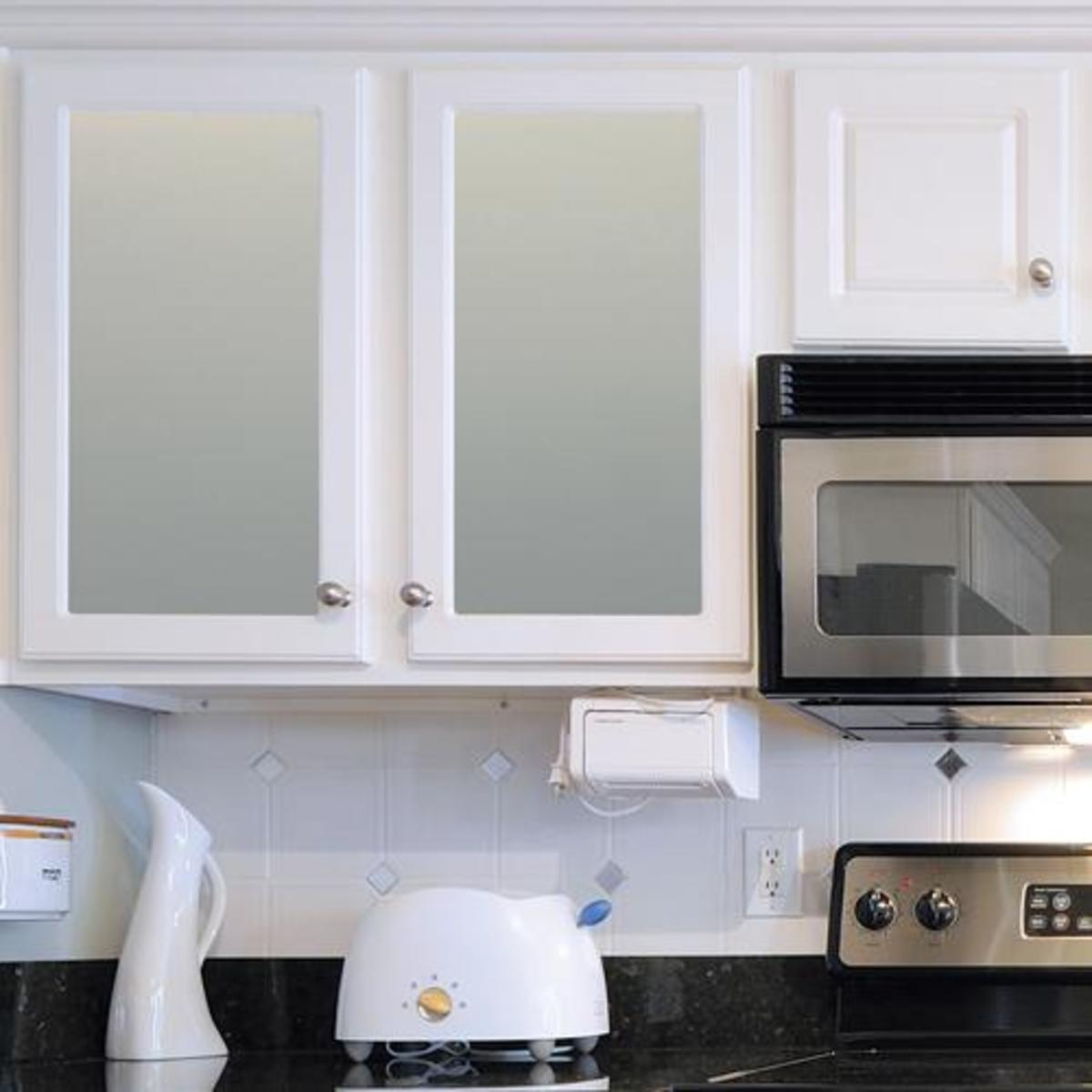 Frosted film over glass helps to obscure your  disorderly kitchen cabinet contents.