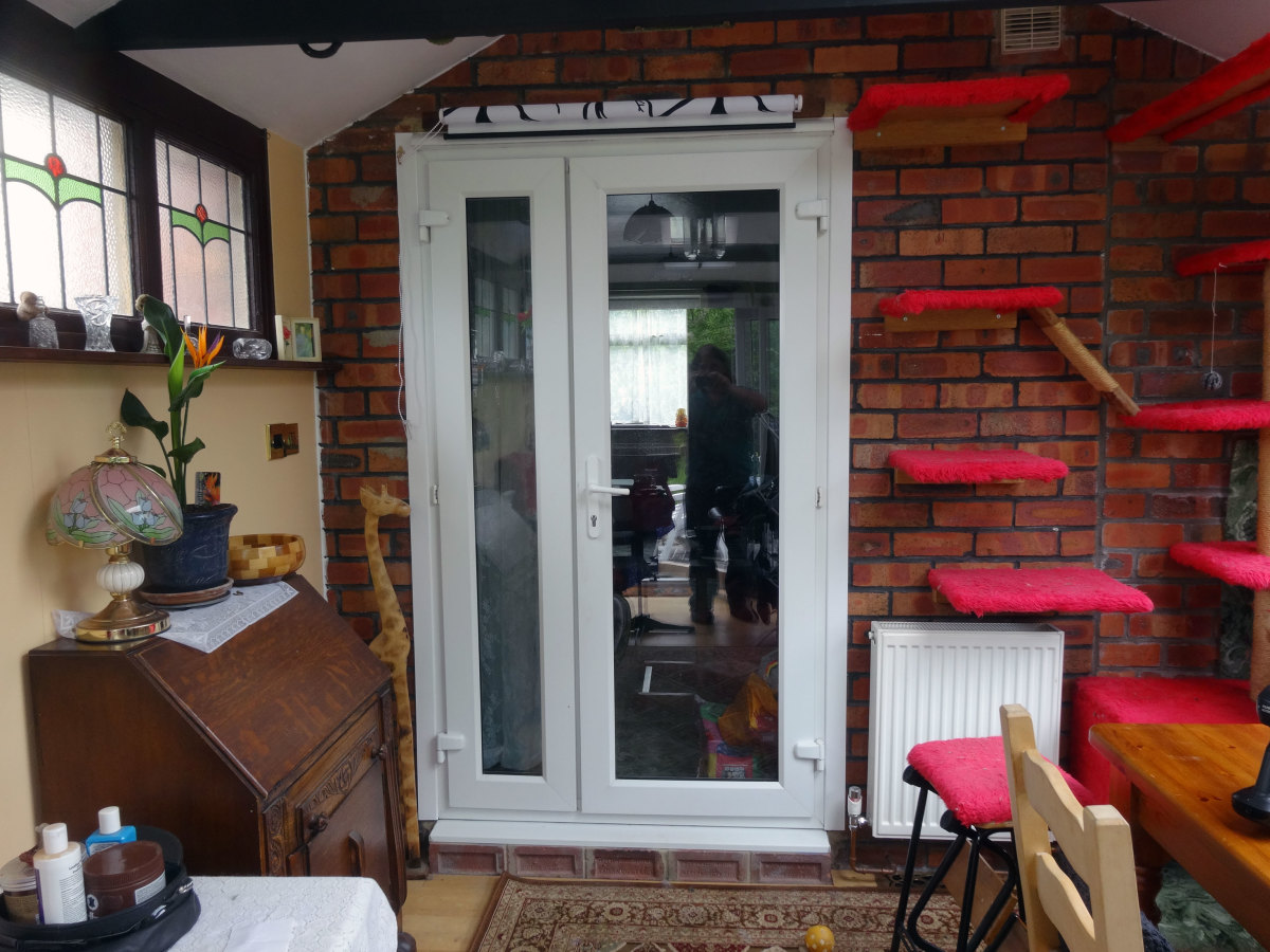 French doors, viewed from conservatory, with roller blind fitted above doorframe.