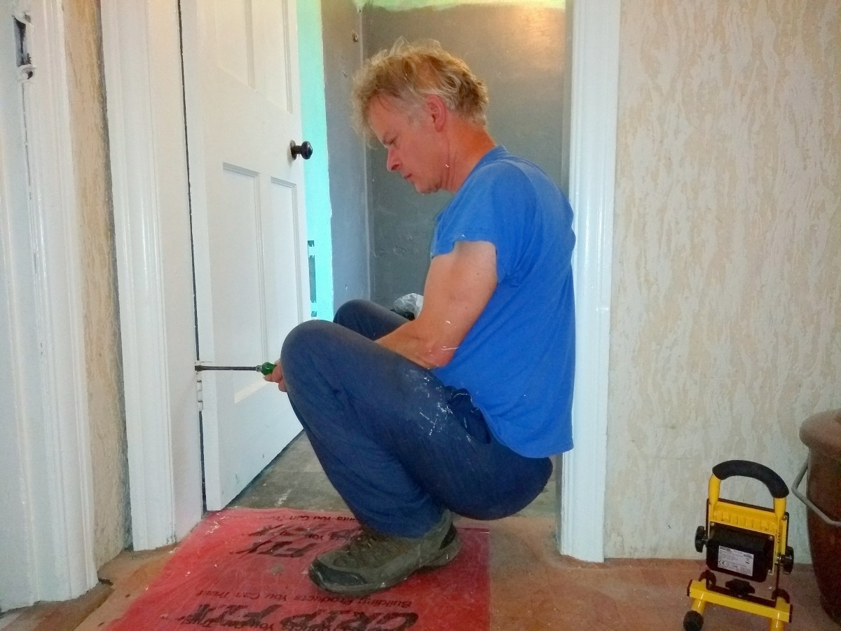 Put your back against the door frame. This enables you to push hard on the screwdriver. Use two hands whilst turning.