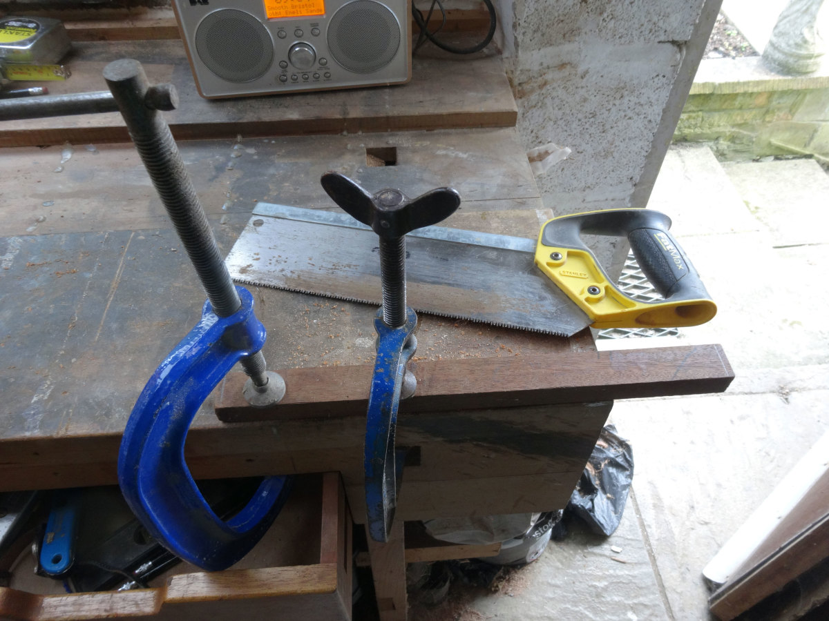 Using a tenon saw to cut the sides of the tenon joint.