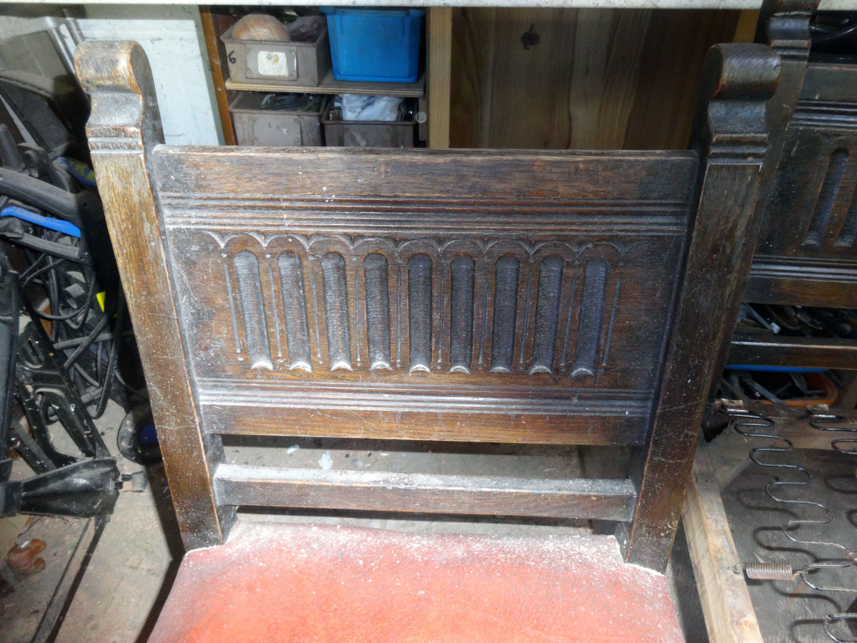 The carved solid oak back of the chairs.