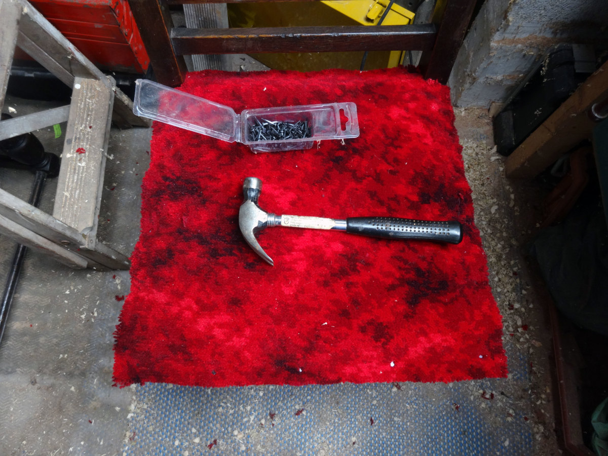 Fixing Axminster carpet to seat with hammer and carpet tacks, as base layer of the seat's padding.