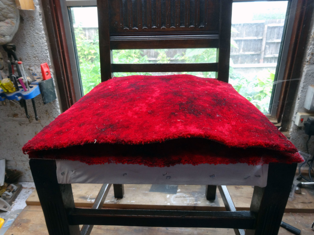 Axminster carpet squares laid in position, and ready to fit the leather seat cover on top.