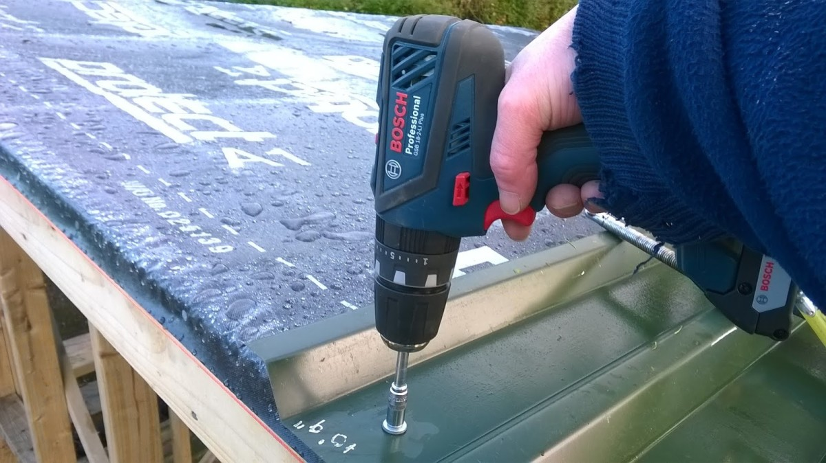 Fixing cladding into place with TEK screws.