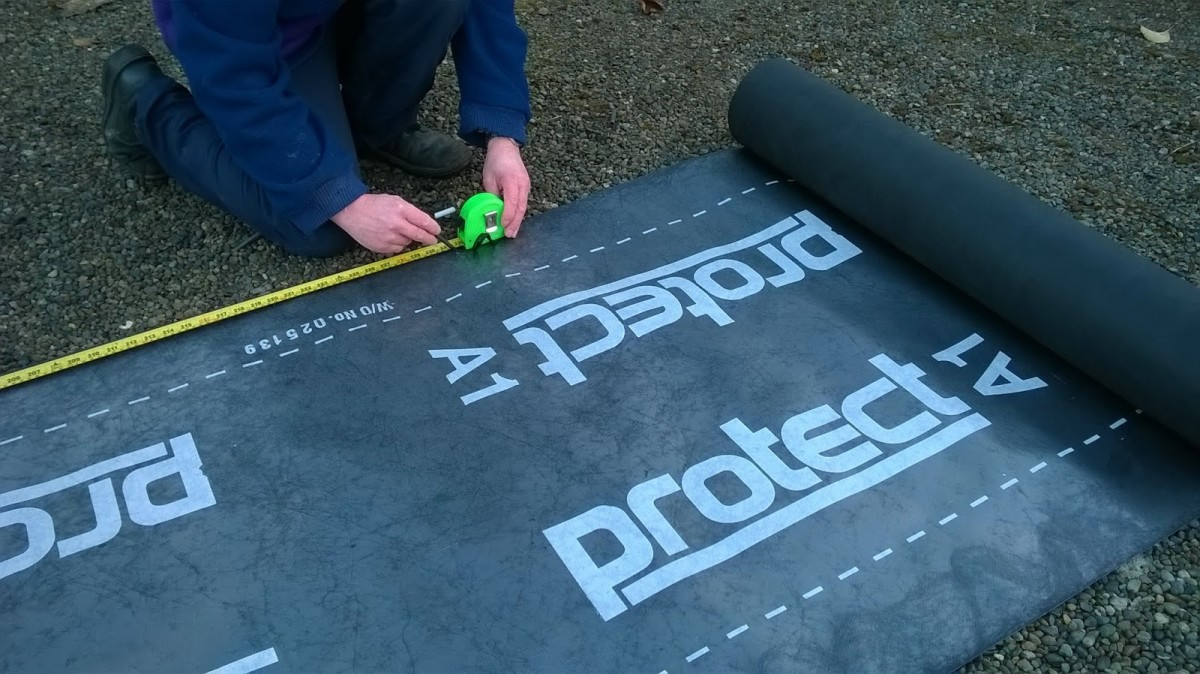 Cutting polypropylene underlay membrane for the roof.