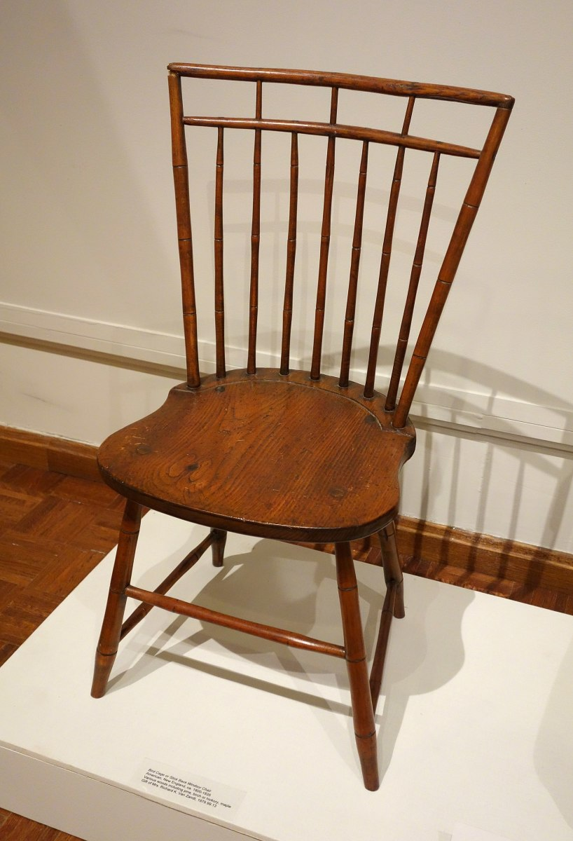 This Windsor chair has no arms and is made of solid, sculpted wood.