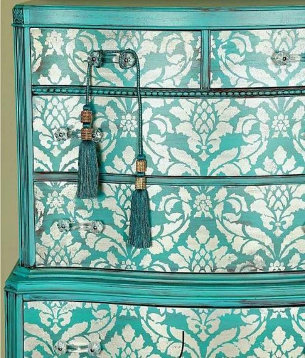 A gorgeous trellis stencil of damask on a highboy dresser.