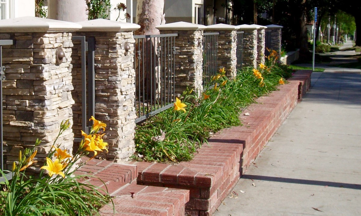 Day lilies planted in a Mediterranean style garden, with stone pillars and brick planter boxes. Ice plants are also commonly used with this style.