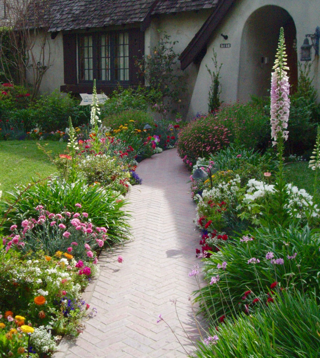 English Country Cottage style. Note the abundance of colorful flowers leading the eye toward the front door. The foxglove in the right rear typifies English style gardens.