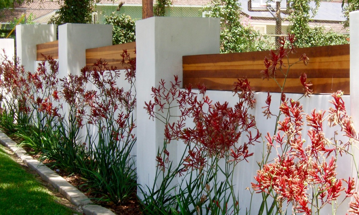 This planting follows along a wall that protects the house behind it. Its line and color match the decorative wood atop the wall and together they keep the eye traveling along the sidewalk area in front.