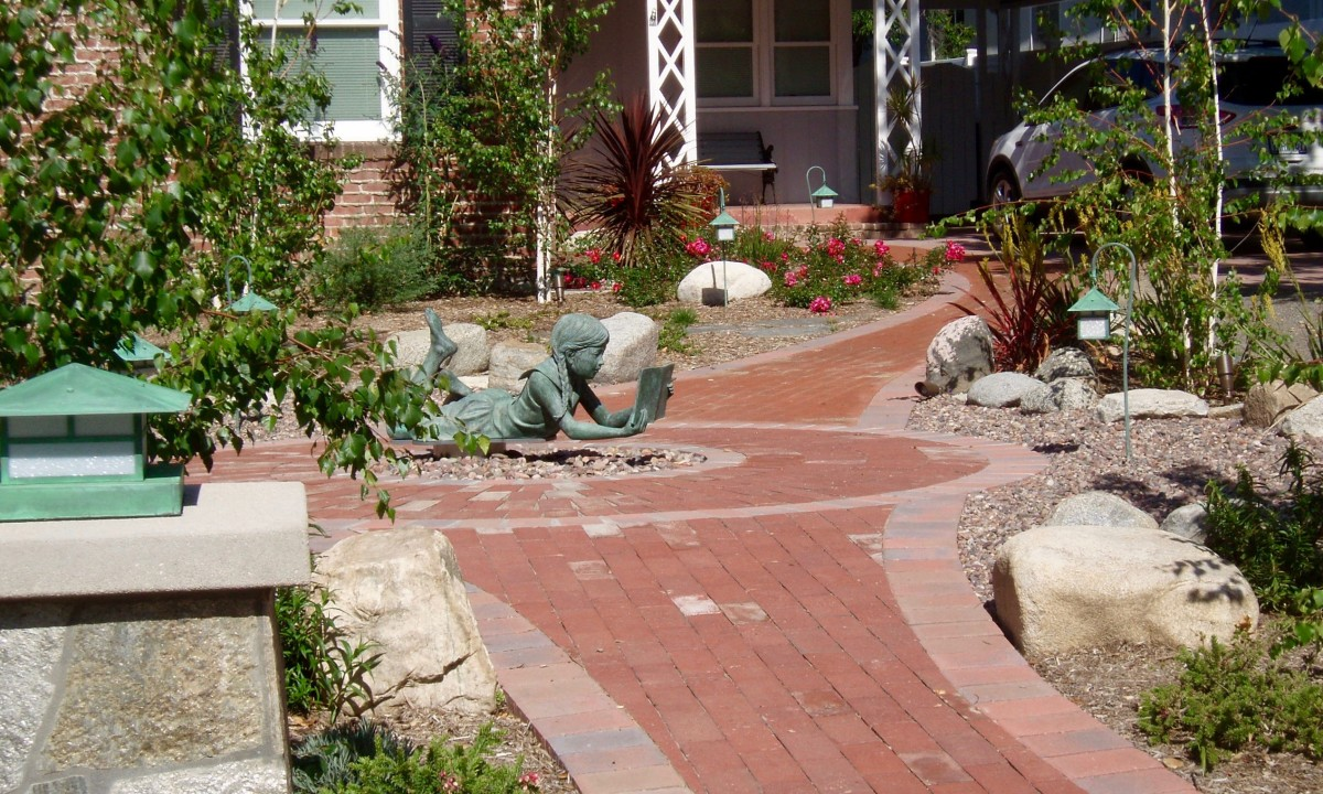 This path and the plants around it lead the eye to the little girl reading on her stomach. From there the next focal point is the potted plants in the doorway beyond.