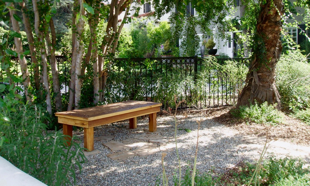 The bench is the main focal point in this landscape, connoting cool shade on a hot summer day. Imagine sitting here with a glass of homemade lemonade while chatting with someone, reading a book, or gazing out at the rest of the garden.