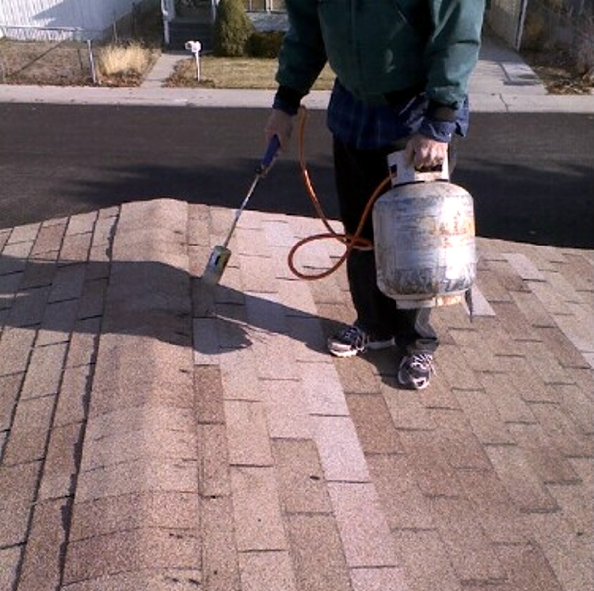 Heating the finished roof repair job with a weed burner to help quick sealing.
