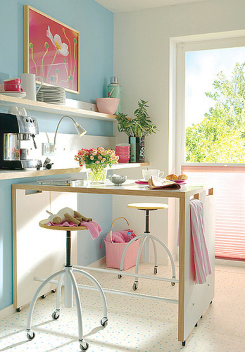 A Nicely Arranged Kitchen with a Wheeled Kitchen Island that can also Serve as a Dining Table