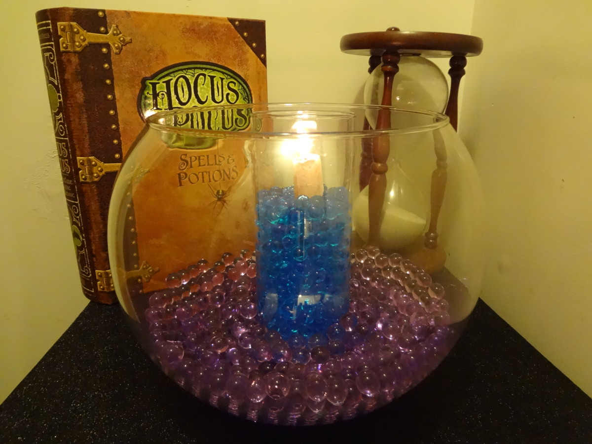 A vase of blue water beads with a candle within a larger bowl of purple beads.