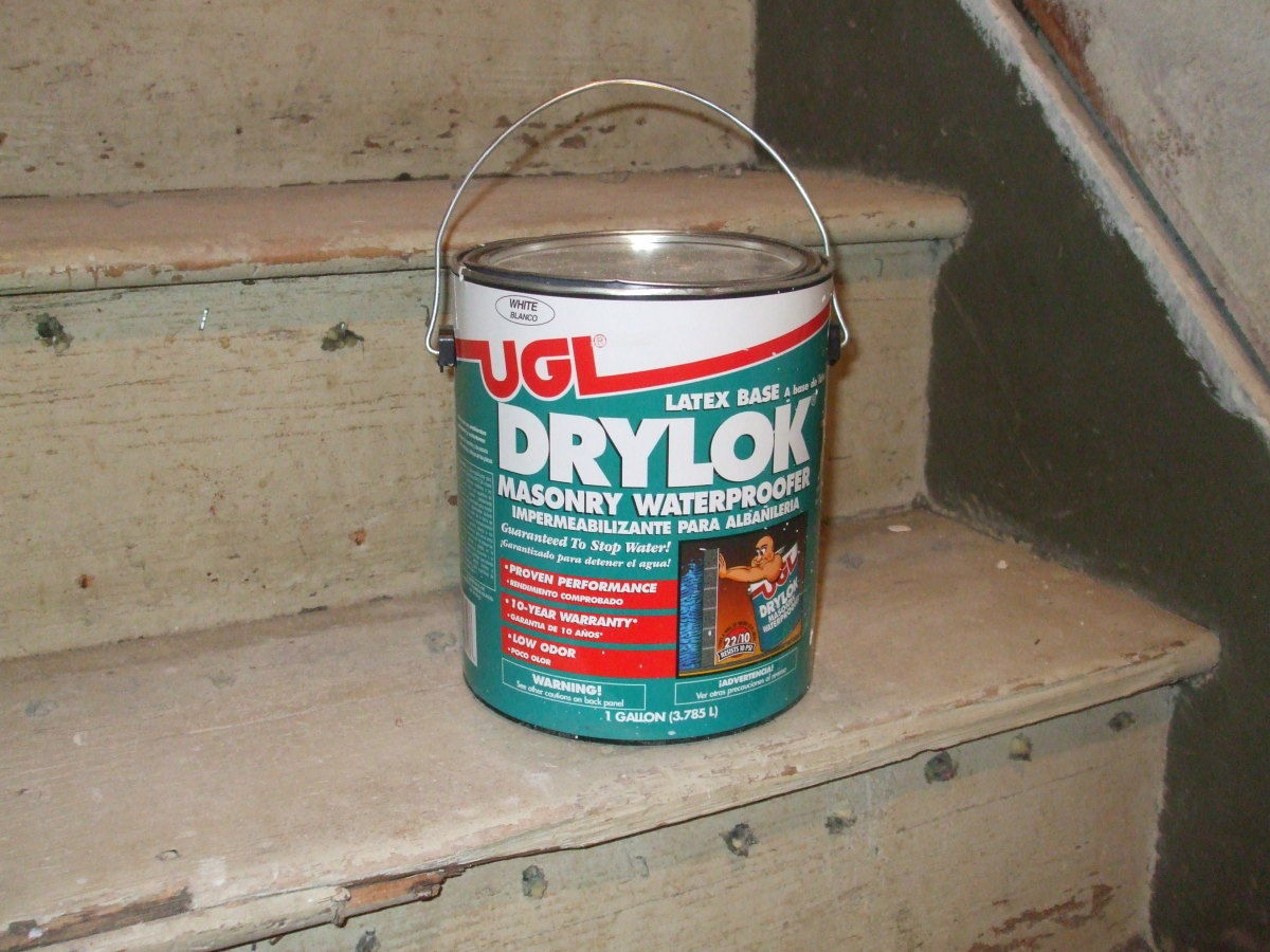 A can of Drylok masonry waterproofing paint sits patiently on old wooden stairs.