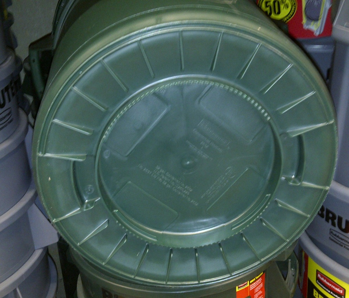 Plastic garbage can with ridges on bottom to resist wearing holes though the bottom
