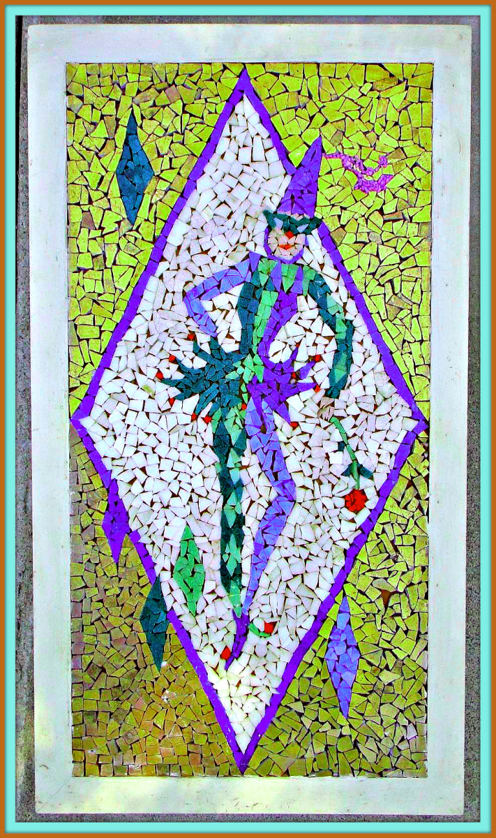 A  vintage mosaic tile wall hanging from the 1950s featuring a jester / harlequin striking a pose with one hand on the hip, while the other is holding a rose.  Framed in a wooden frame.  Tile colors are white, green, purple, gold, and red.