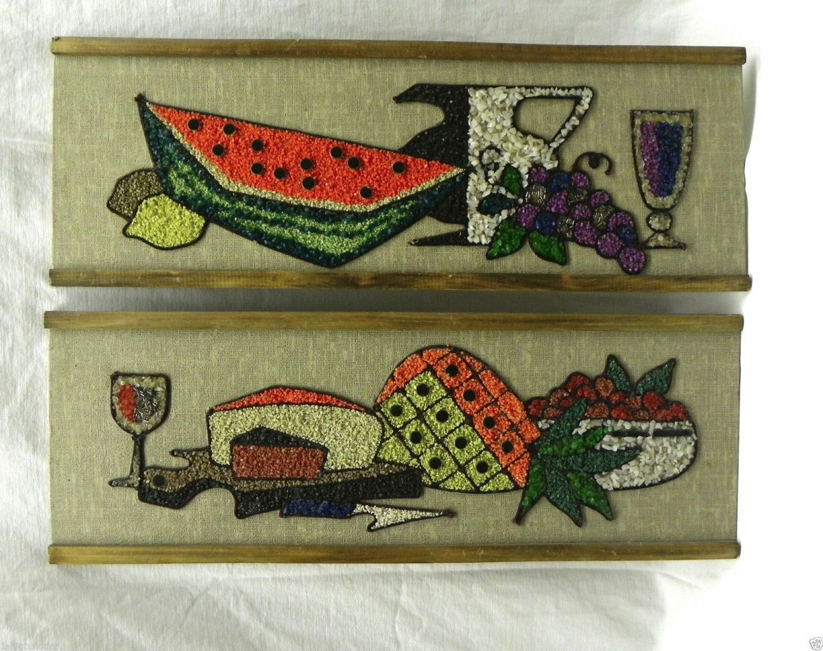 This is a set of two gravel art pictures in excellent condition. It has a beige woven fabric background mounted on Masonite with a wood frame on two sides. The mosaic features a still life arrangement with a wine goblet, cheese wedges, and fruit.