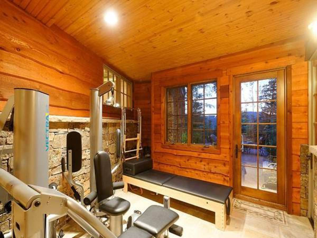 A warm and inviting pine-paneled rustic home gym complete with stone wainscoting on the walls