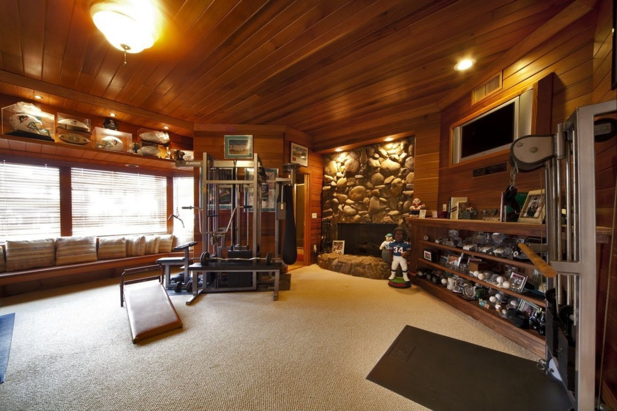 Warm and Inviting Home Gym with Wood Ceiling and light beige carpet and stone fireplace