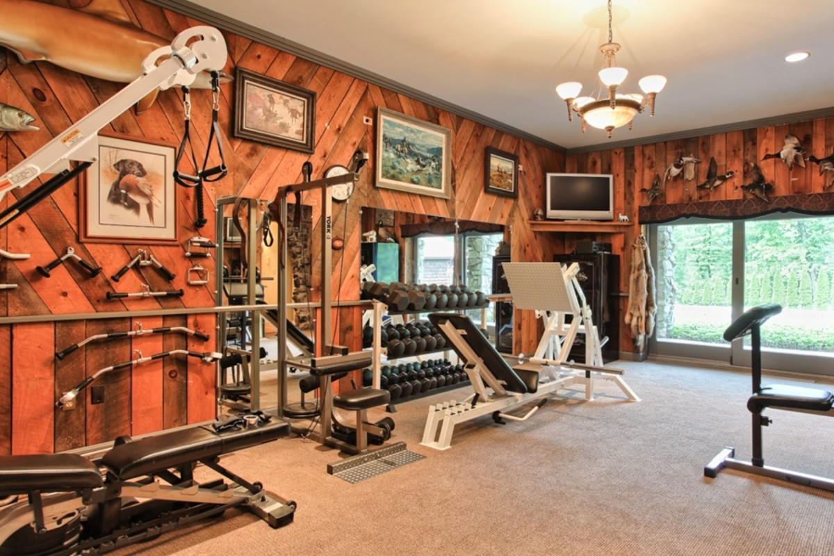 Beautiful Rustic Home Gym with a Lodge Feeling with framed paintings of hunting scenes and taxidermy foul decorating the walls
