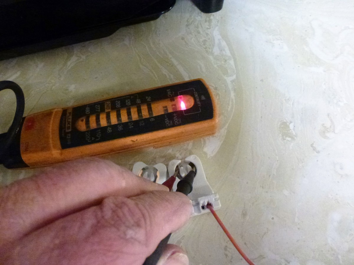 Testing the old tombstone.  With a probe on each of the metal contacts where the lamp goes, the meter shows that they are connected together internally.  This tombstone is not appropriate for a single ended LED lamp.