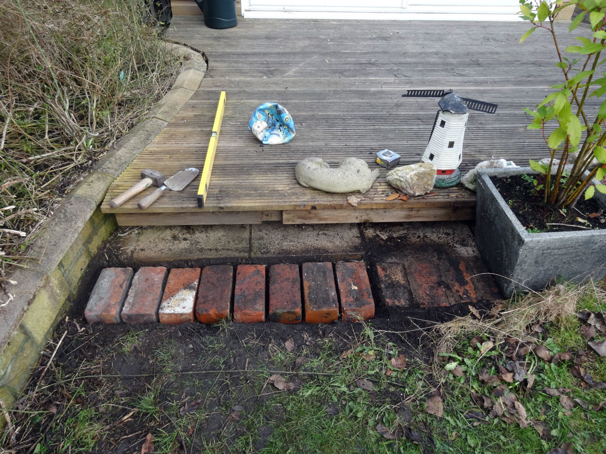 As the lawnmower can't get into tight spaces, laying bricks in small gap in front of decking before laying the boundary wire.