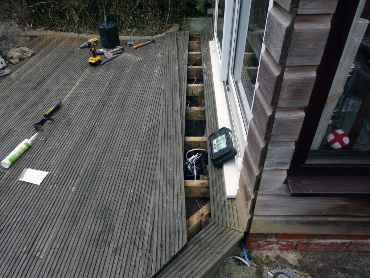Decking board lifted to gain access for cabling.