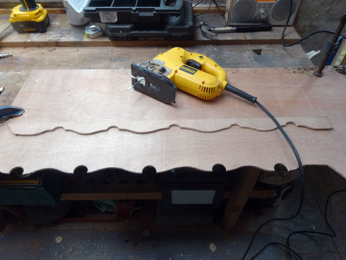 Using a jig saw to cut the wavy lines between the circular holes cut in the plywood; to make the new decorative trim match the original.
