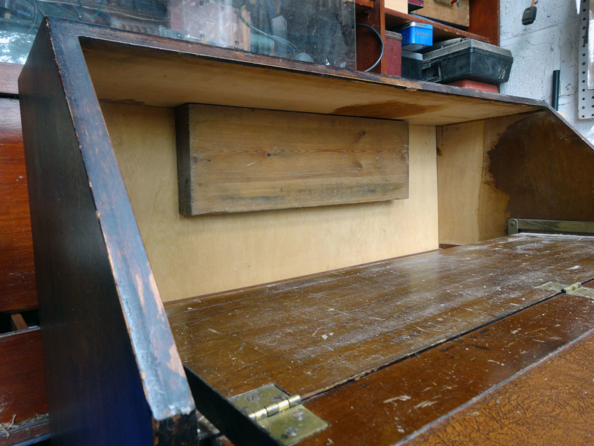 2 inch thick timber fixed to back of bureau so that the pigeon-holes can be butted against it to give a solid fixing.