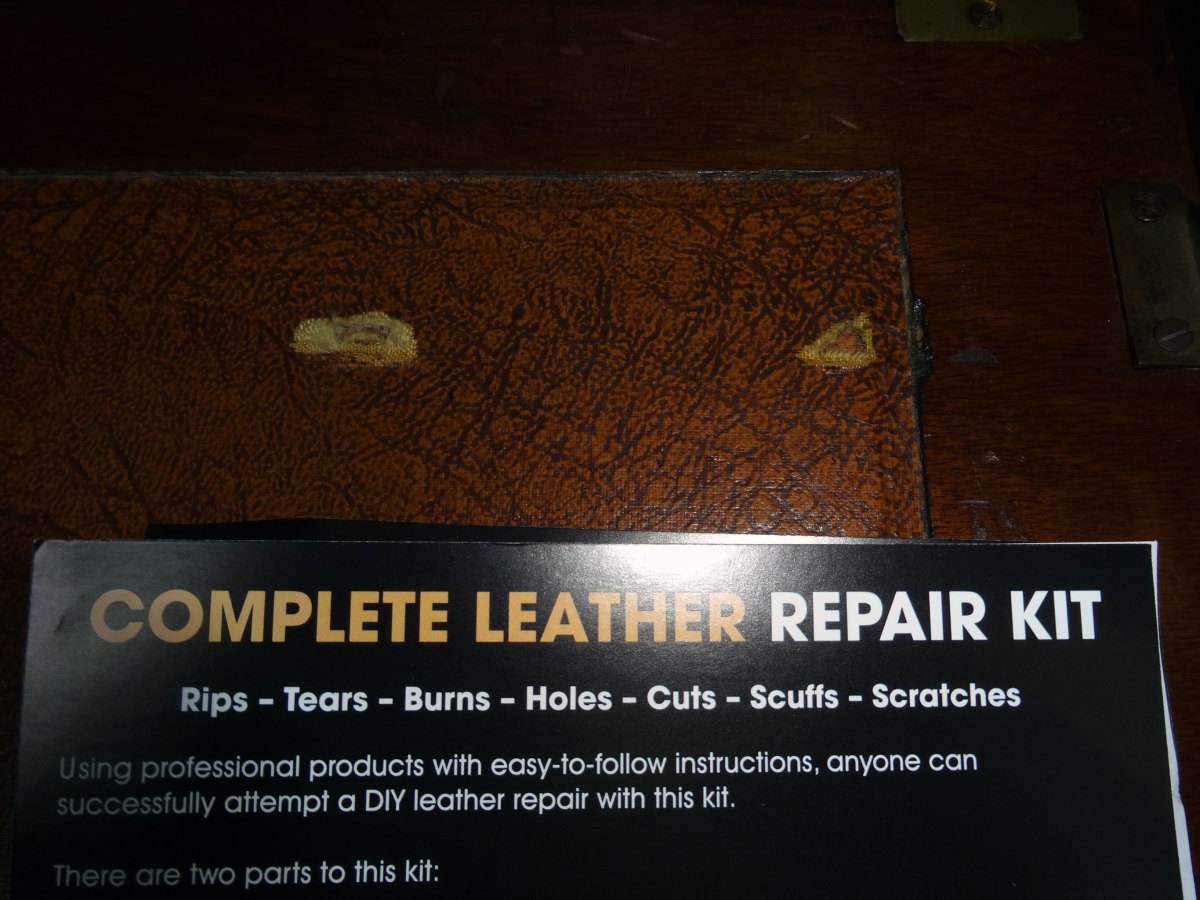 The two holes in the leather inlay that need to be repaired.