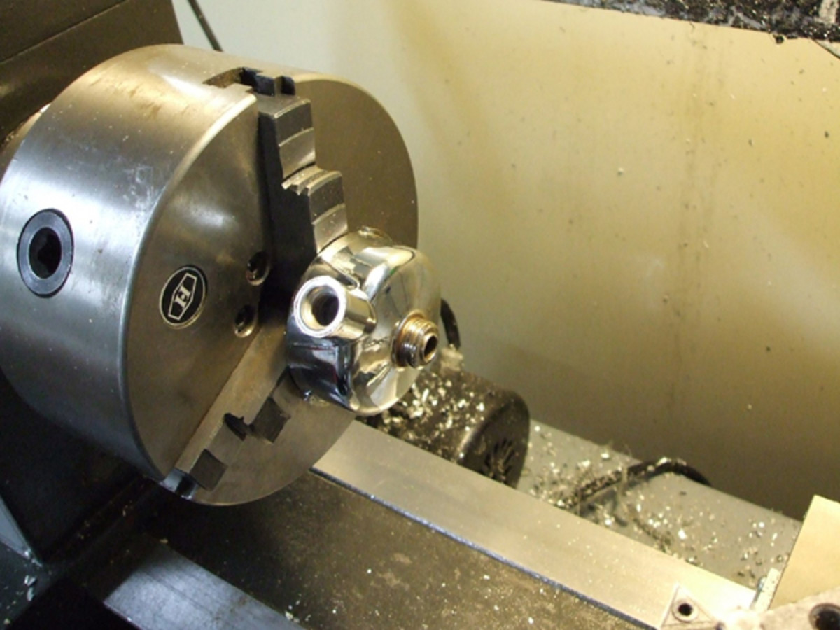 Here is the portafilter clamped into the lathe on a 3-jaw chuck.