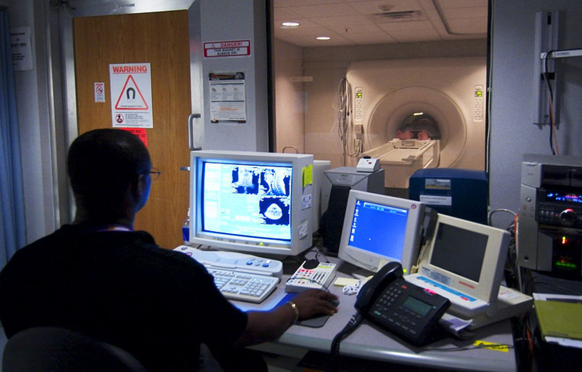 A civilian technician watches as a patient goes through an MRI machine at the National Naval Medical Center in Bethesda, Maryland.