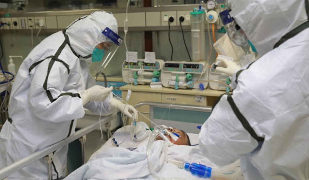 Health workers in protective suits in treating patient with COVID-19
