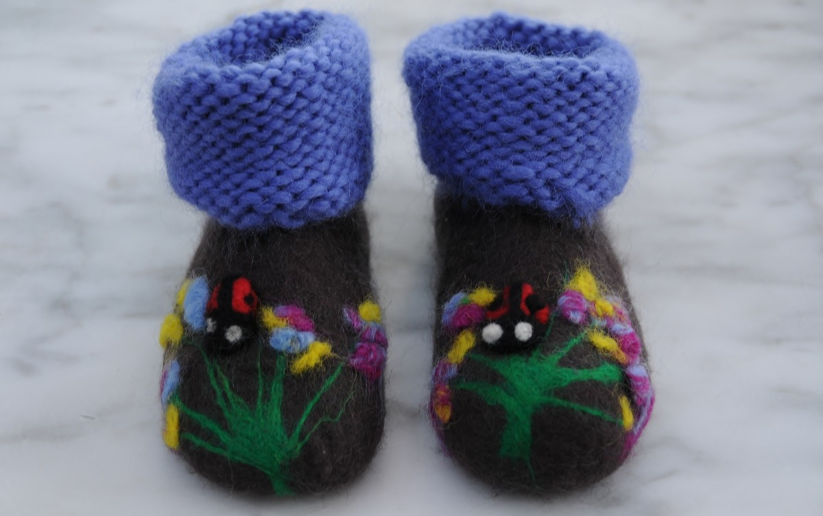 The completed booties, a cute floral scene and a pair of needle felted ladybirds!