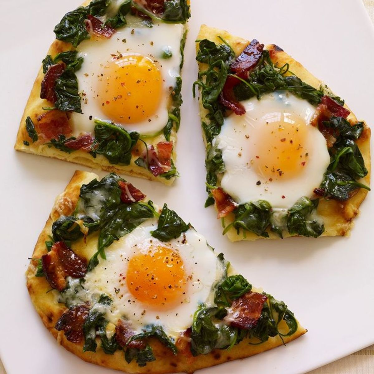 Breakfast Pizza With Sunny-Side Up Eggs, Spinach, and Bacon