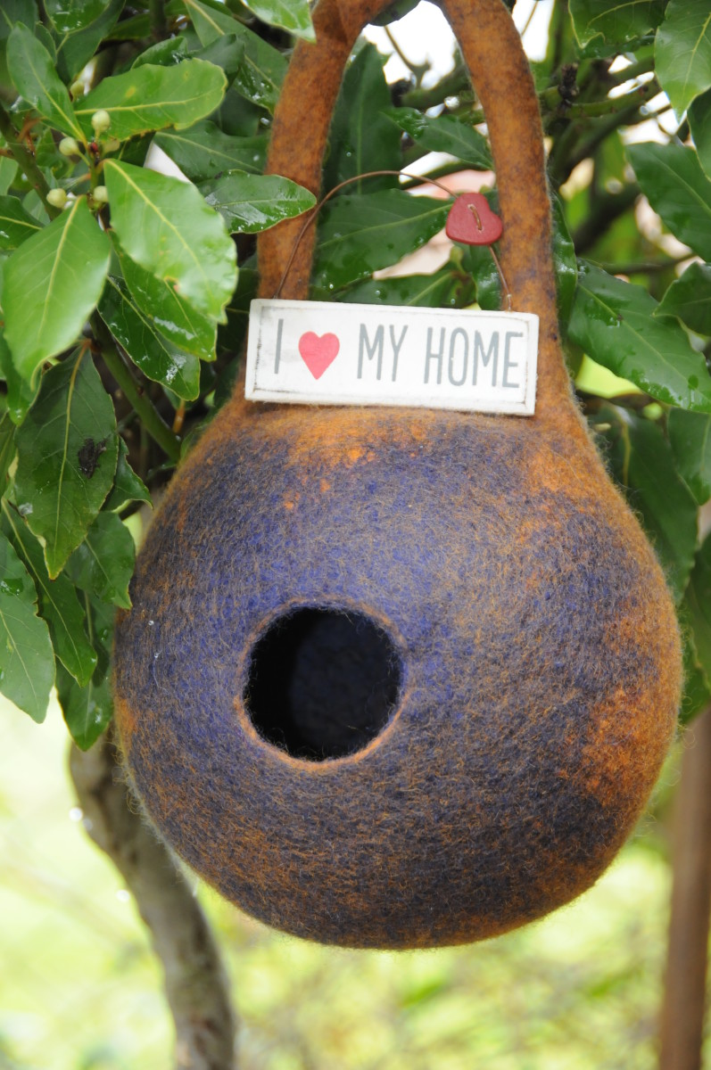 The completed wet-felted bird pod project with a cute sign.