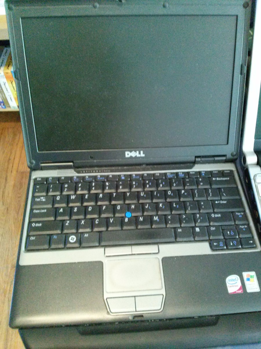 The Dell Latitude D430 has some dust on the screen, hard to see in photo, and some greasy finger marks on the keys and trackpad.