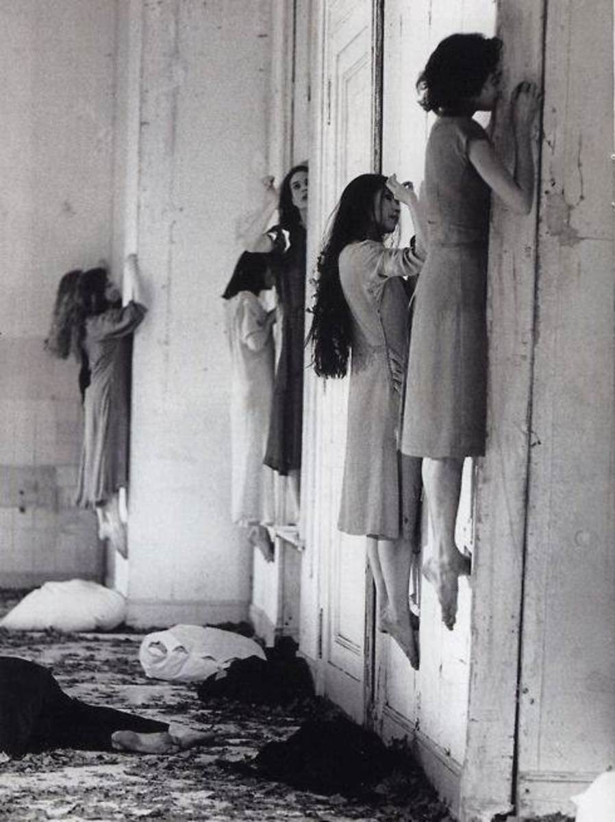 Creepy girls hovering, unsupported against the wall