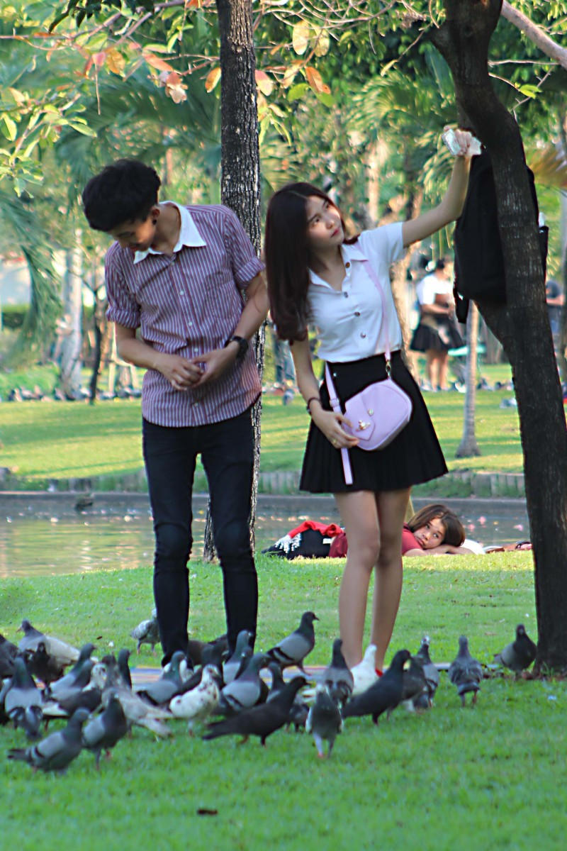 A young couple. He feeds the birds while she photographs herself - typical!