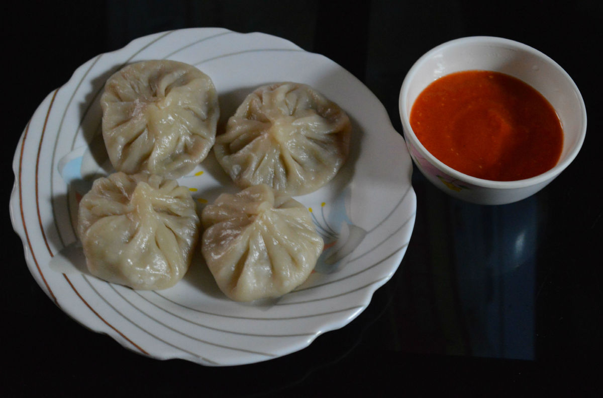 Homemade vegetarian momos with tomato dip.