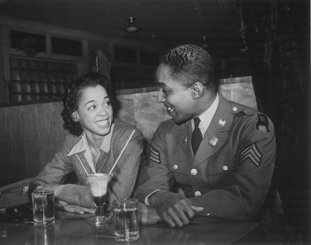 """Sergeant Franklin Williams, home on leave from Army duty, with his best girl Ellen Harden, splitting a soda"""