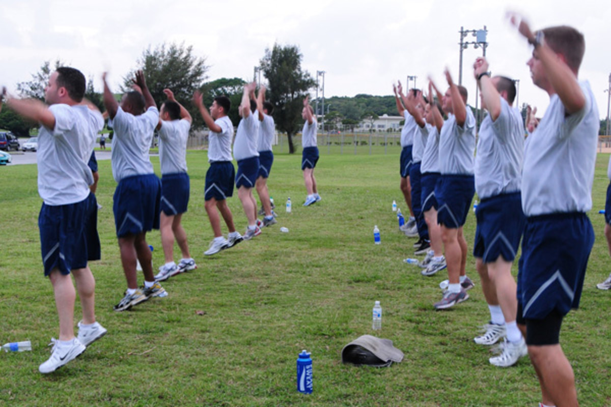 Airmen performing side straddle hops, otherwise known as jumping jacks.